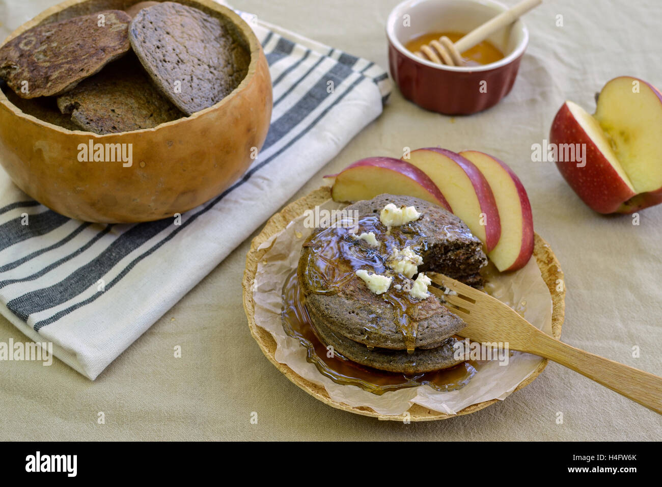 Rustic meal of buckwheat pancakes in plate and bowl made of gourds, on flower sac tablecloth, accompanied by maple - Stock Image