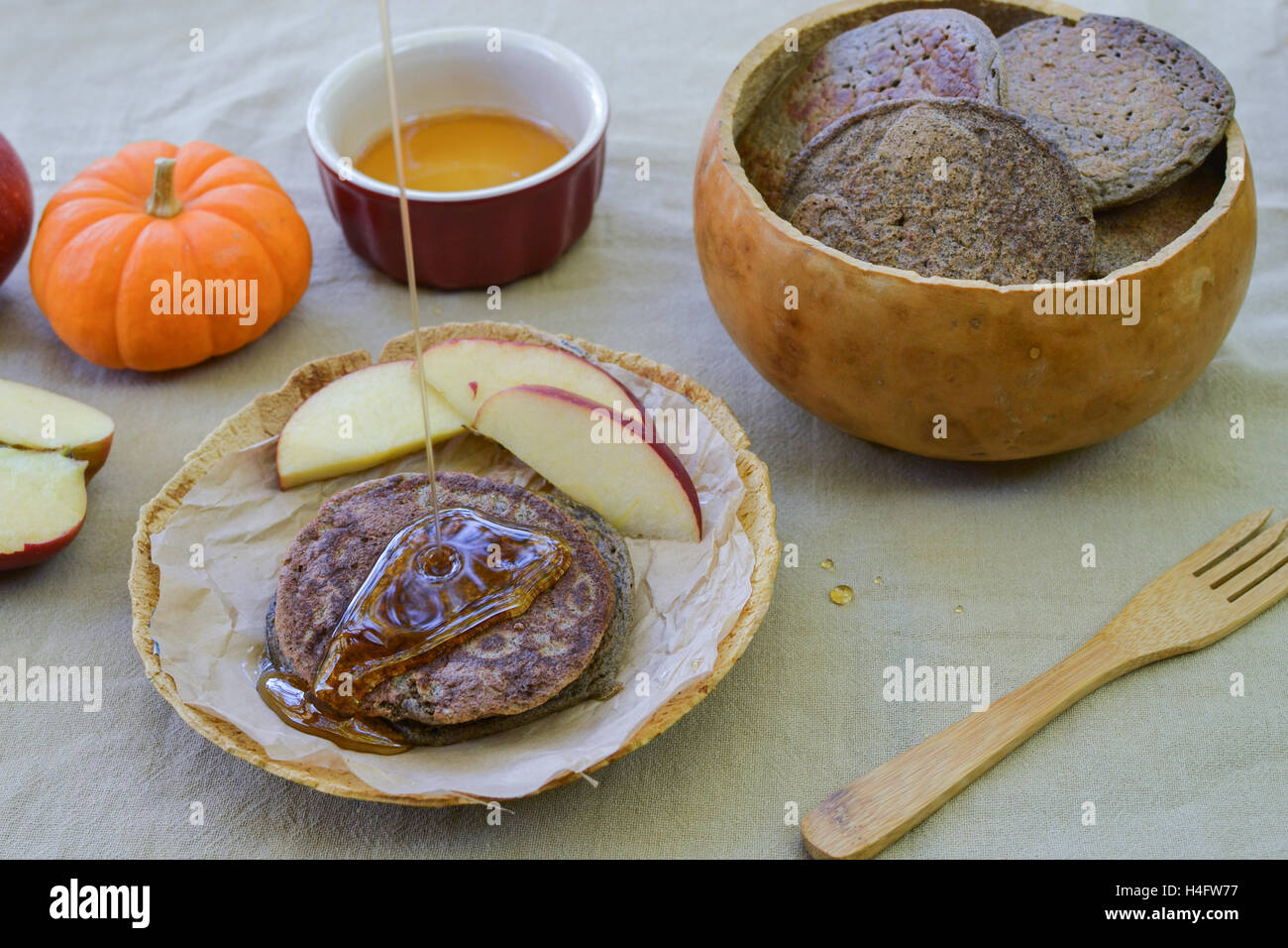 Rustic meal of buckwheat pancakes in plate and bowl made of gourds, on flower sac tablecloth, accompanied by maple Stock Photo