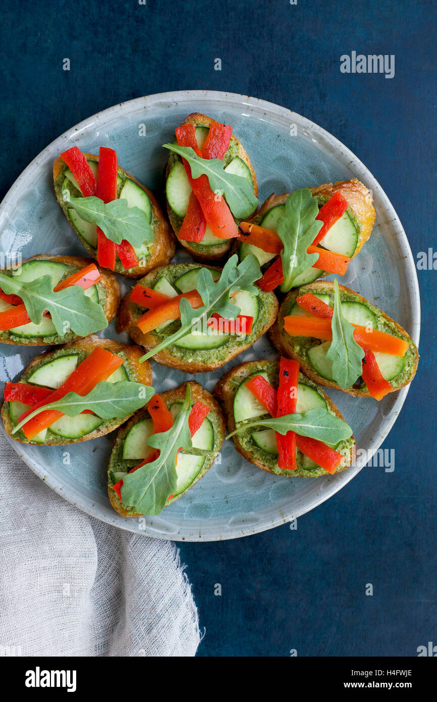 Chive Crostini with Cucumber, Roasted Red Pepper and Aruglua photographed from top view on a dark blue background. - Stock Image