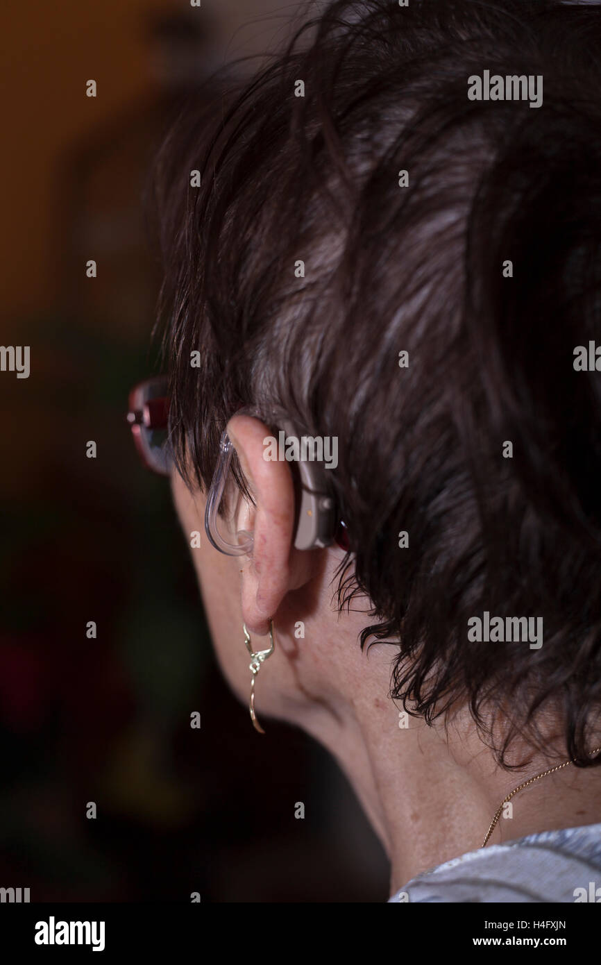 Detail of a senior woman head with hearing aid. - Stock Image
