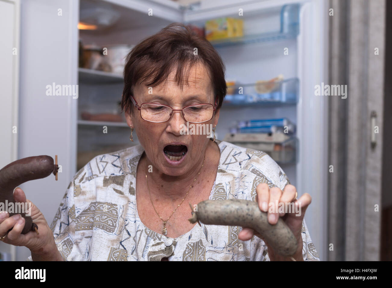 Shocked senior woman holding pork liver sausages while standing in front of the open fridge in the kitchen. - Stock Image