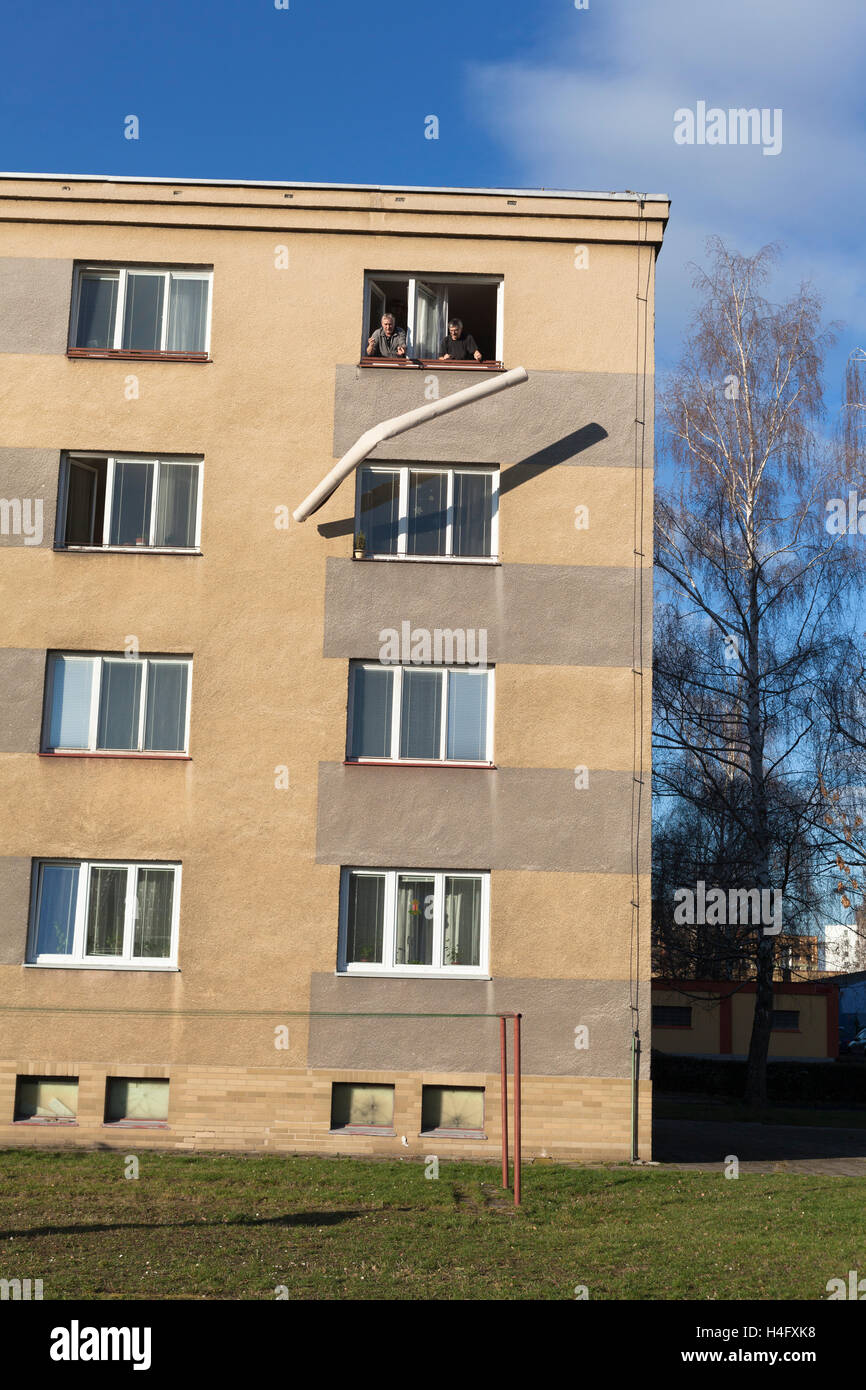 Two seniors throwing rolled carpet out of a window from the top floor of a building. - Stock Image