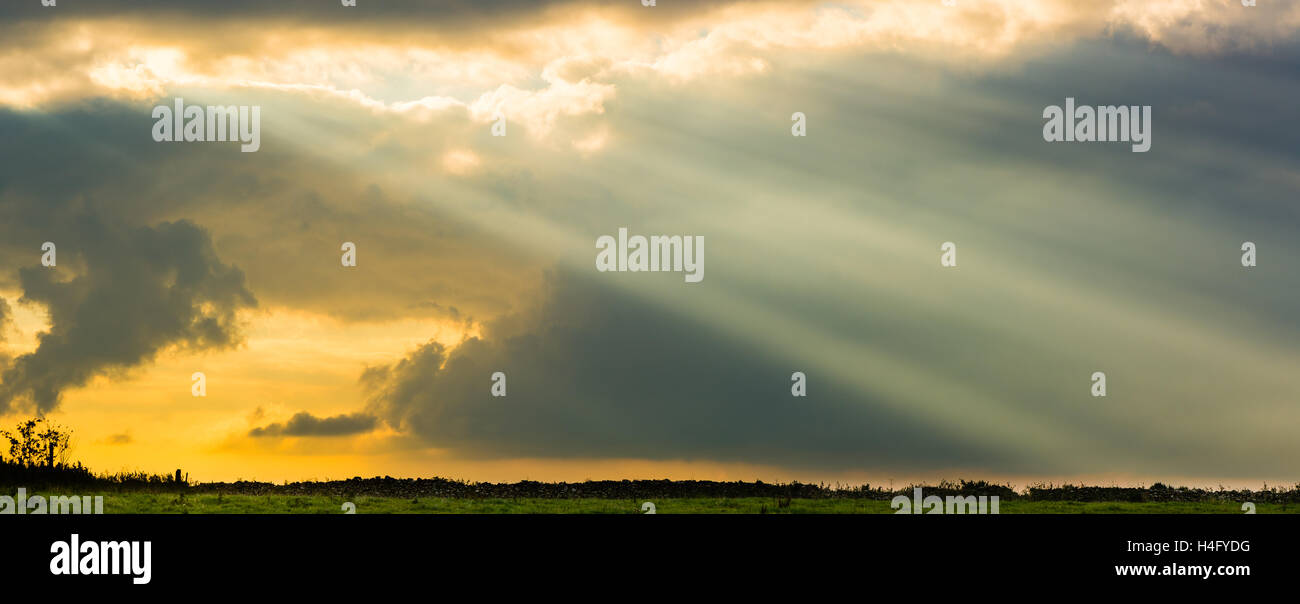 Sun rays from clouds above field and dry stone wall. Impressive angry sky with sunshine, above pasture in English - Stock Image