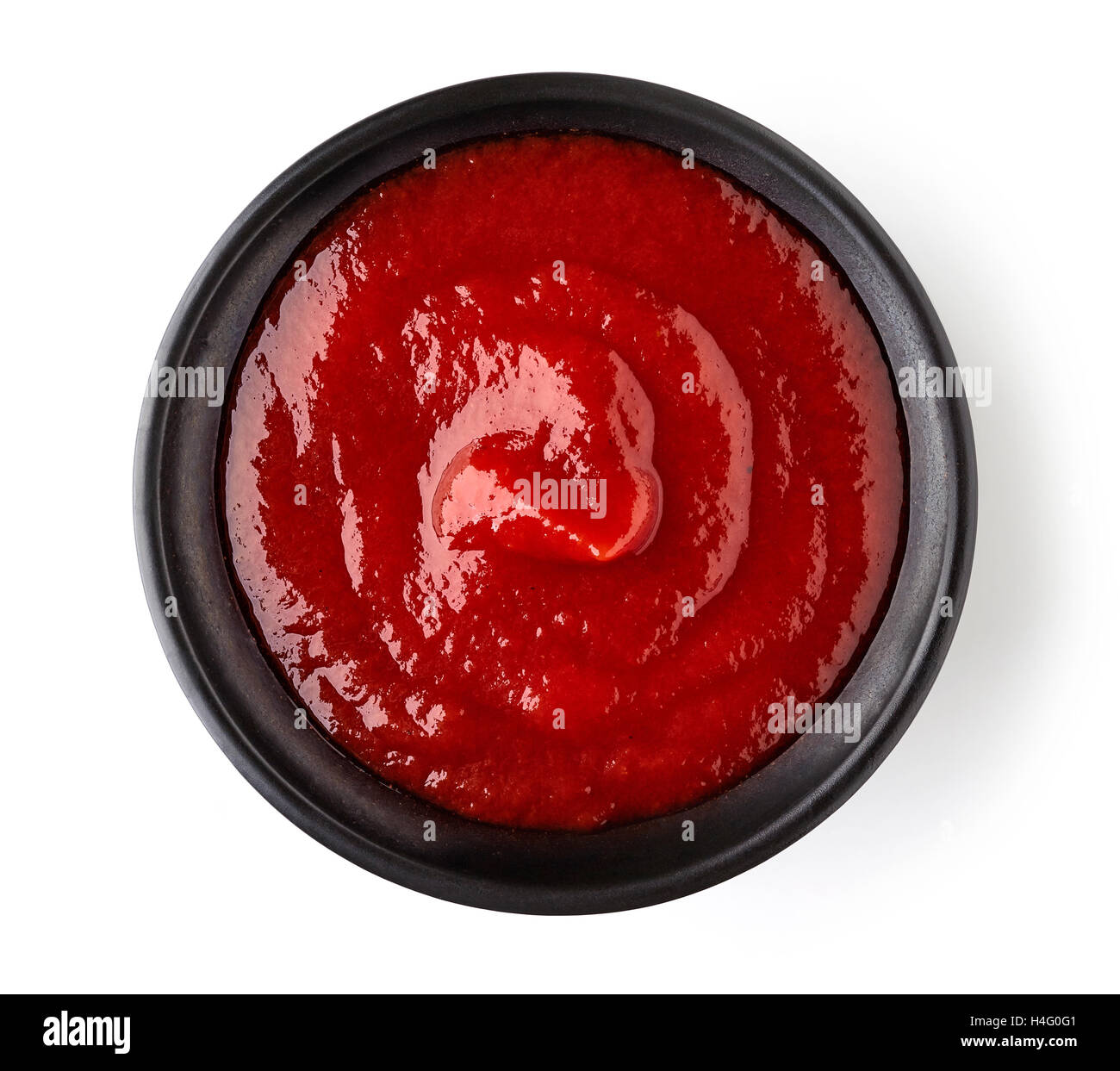 Bowl of ketchup or tomato sauce isolated  on white background, top view - Stock Image