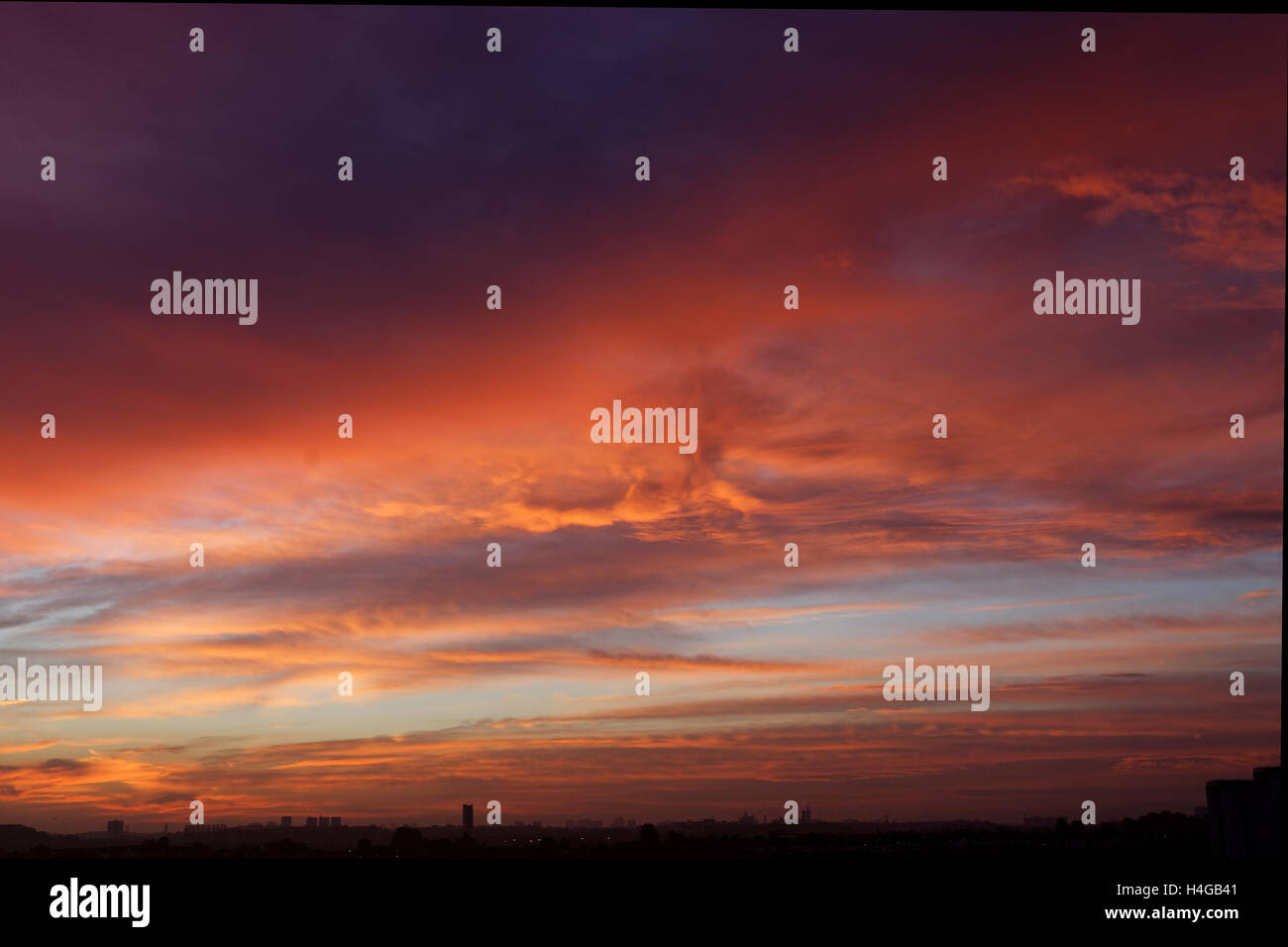 Stunning red shepherds warning sky over Glasgow as the sun rises - Stock Image