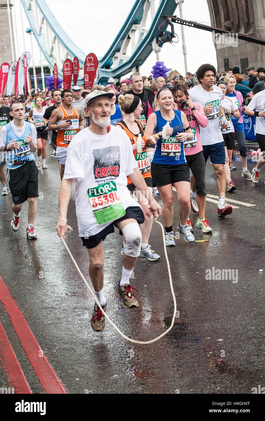 Runners participating running in iconic London Marathon,England. Mature,senior,old,mature,elder,elderly,man, skiipping - Stock Image