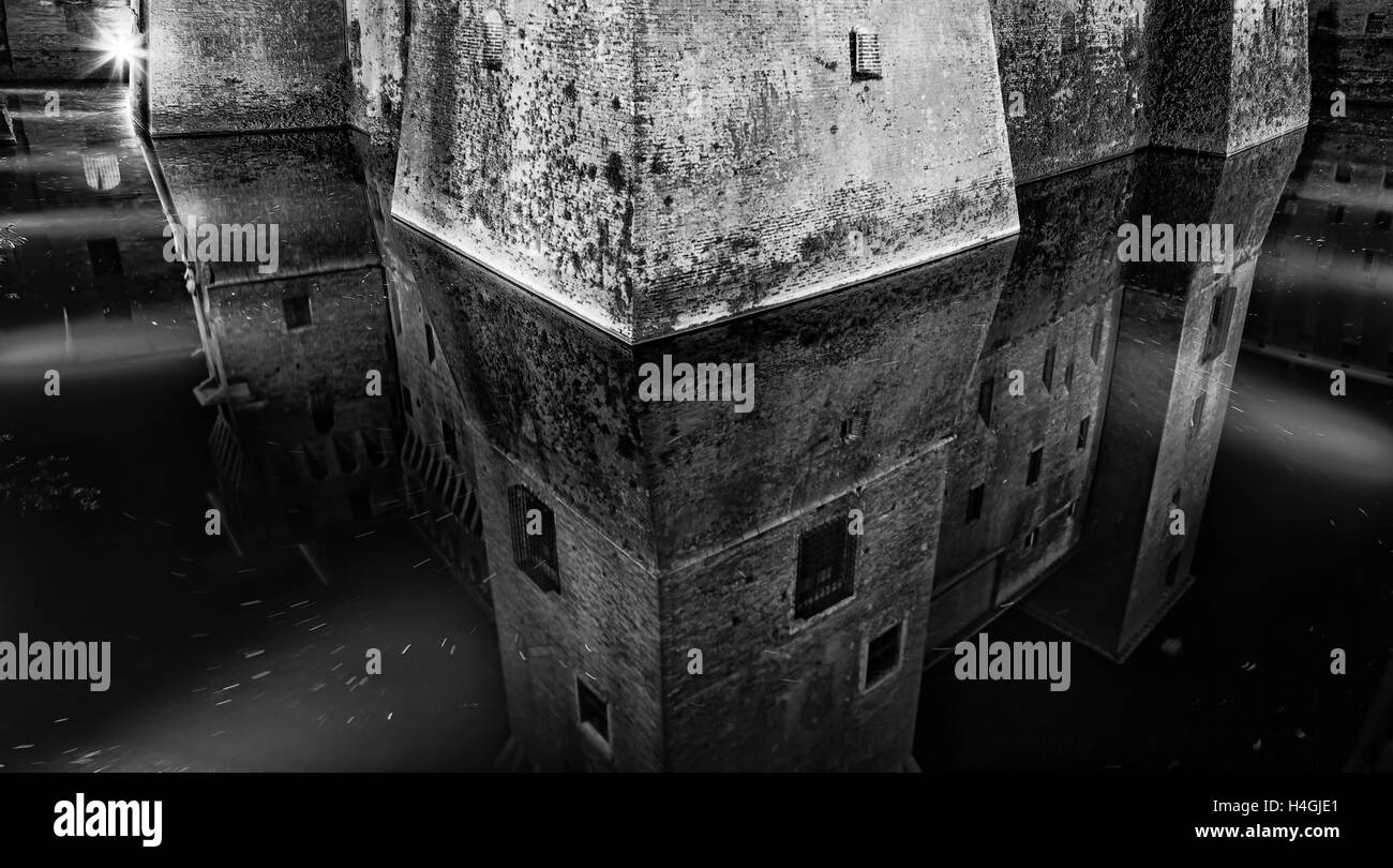 Corner fortification stone tower of ancient feudal castle in Mantua city of Italy. Water moat reflects powerful - Stock Image