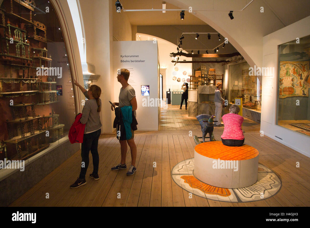 Visitors peruse folk art exhibits at the Nordic Museum in Stockholm, Sweden. - Stock Image