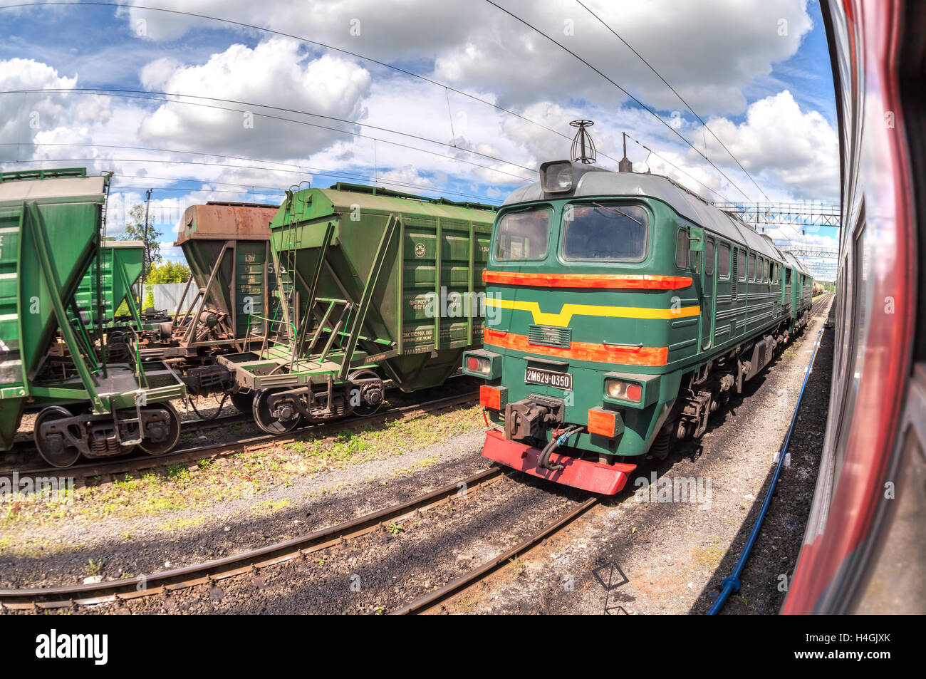 Freight train standing at a railway station in summer day. Cargo train logistic - Stock Image