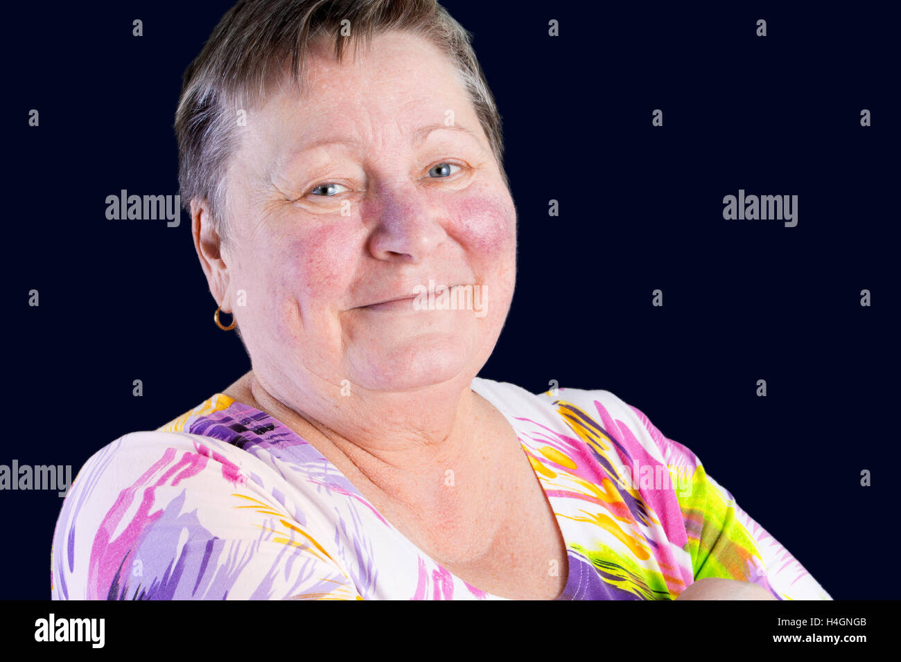 Portrait of happy and smiling senior woman in photo studio isolated on dark blue background Stock Photo