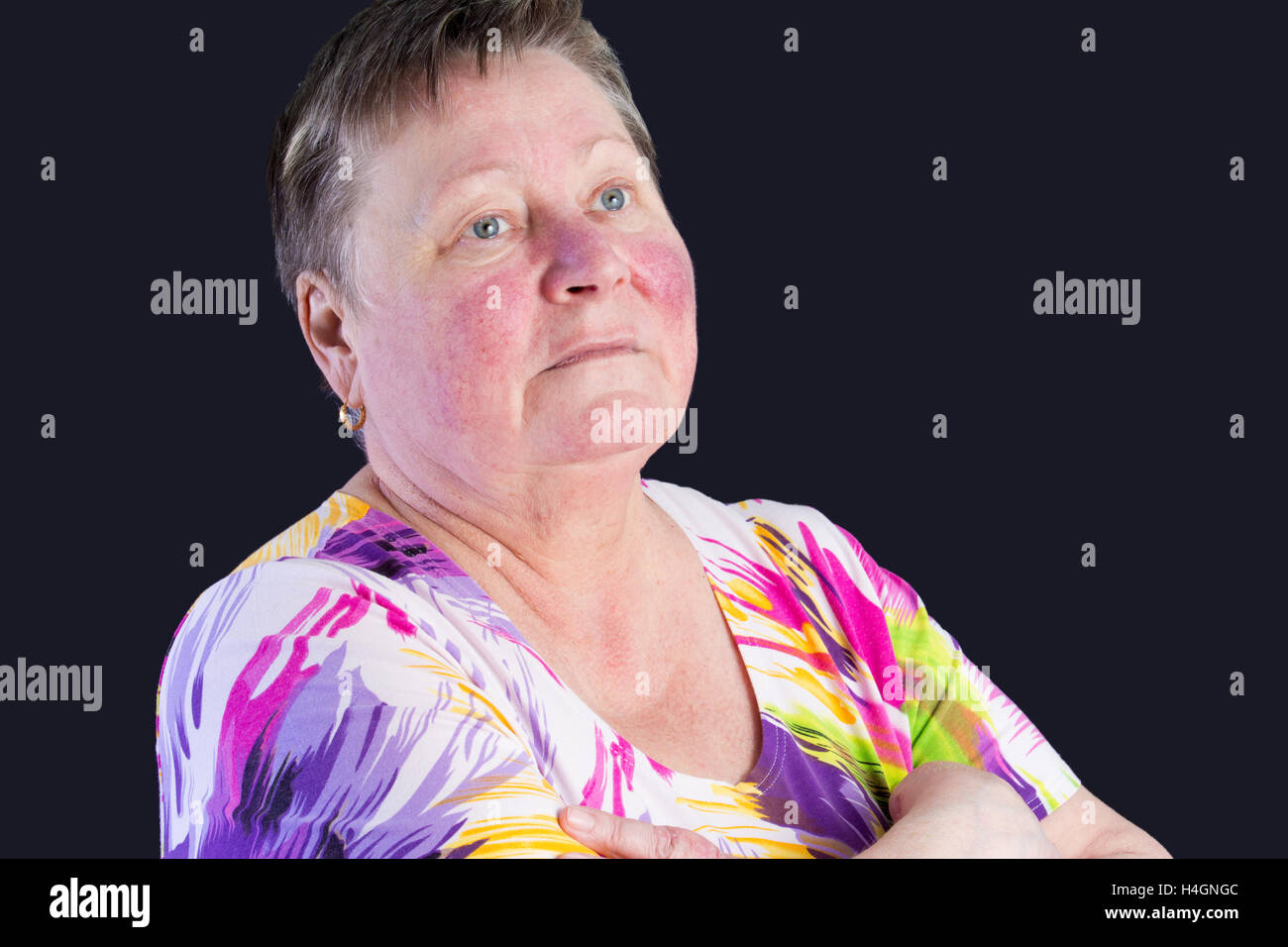 Portrait of unhappy sad senior woman in photo studio isolated on dark blue background Stock Photo