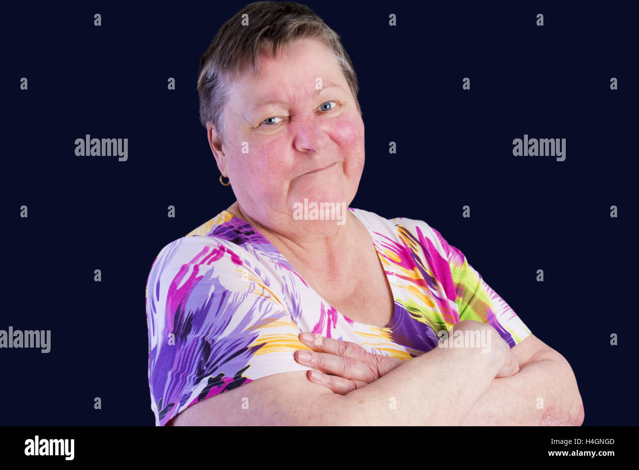 Portrait of disappointed senior woman with grimacein photo studio isolated on dark blue background Stock Photo