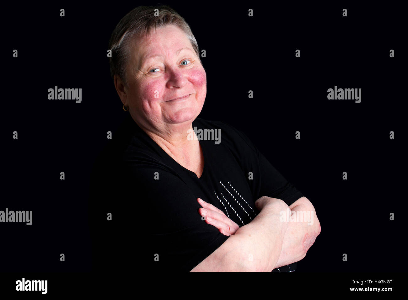 Portrait of happy and smiling senior woman in photo studio isolated on black background Stock Photo