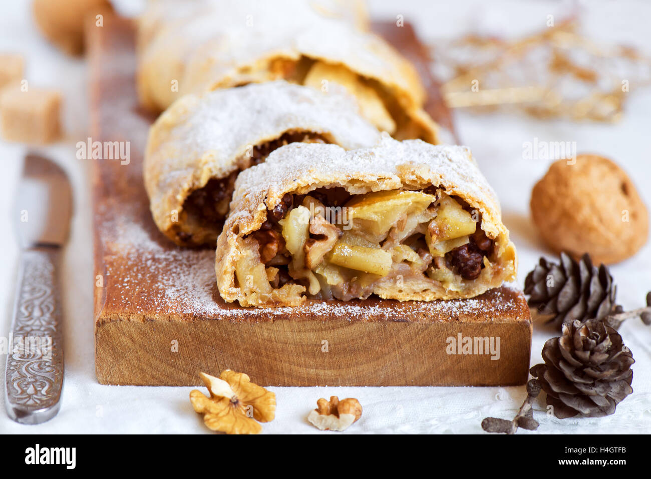 Christmas homemade pastry. Apple strudel (pie) with raisins, walnuts and powdered sugar with Christmas decor close - Stock Image
