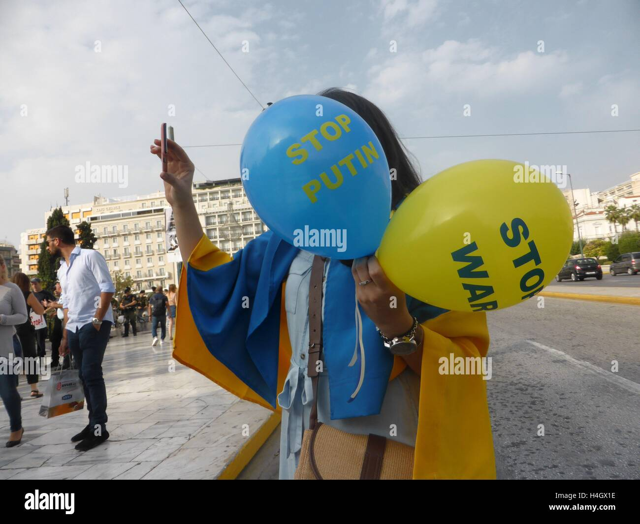 Athens, Greece. 16th Oct, 2016. A demonstrator holds ballons with the messages 'Stop Putin' and 'Stop War' on them. Stock Photo