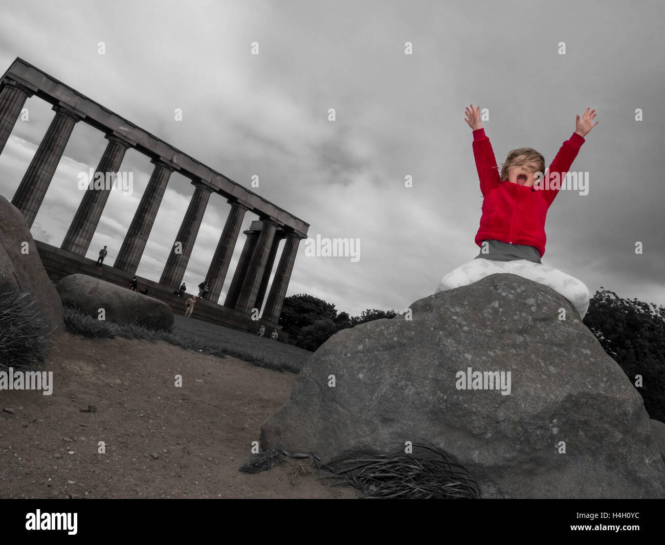 Little girl sitting on the big rock with her hands up in the air and shouting loudly - Stock Image
