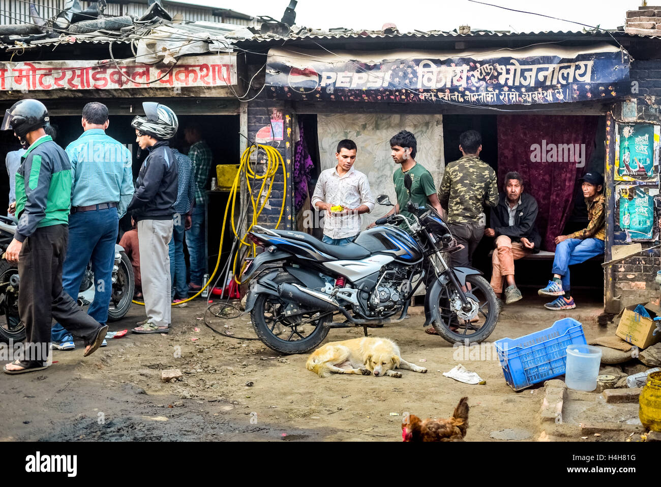 A crowd gathers at a motorcycle repair shop on Sunday morning in the outskirts of Kathmandu, Nepal. - Stock Image