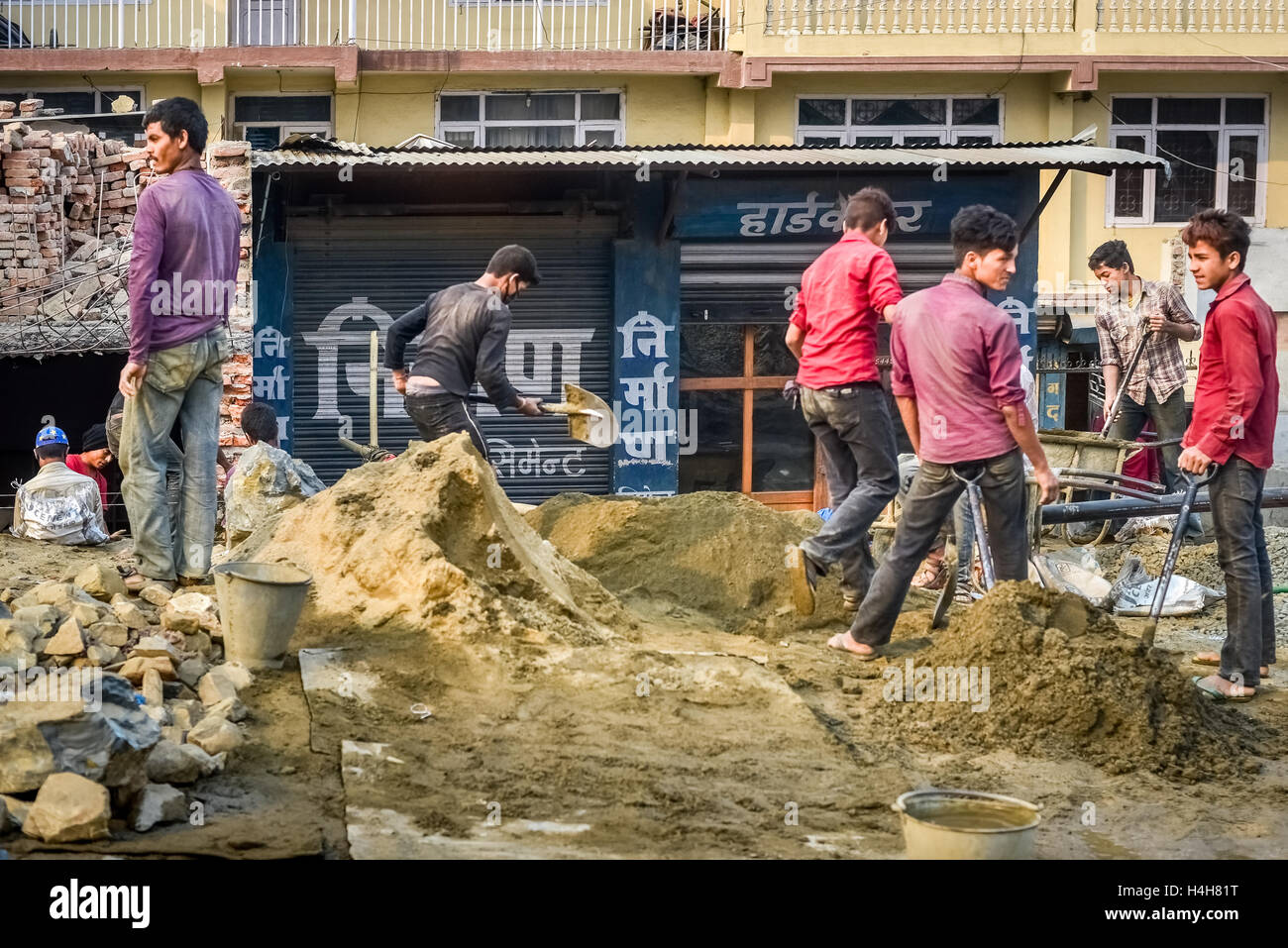 Young men working with mixed materials to build houses in the outskirts of Kathmandu, Nepal. © Reynold Sumayku - Stock Image