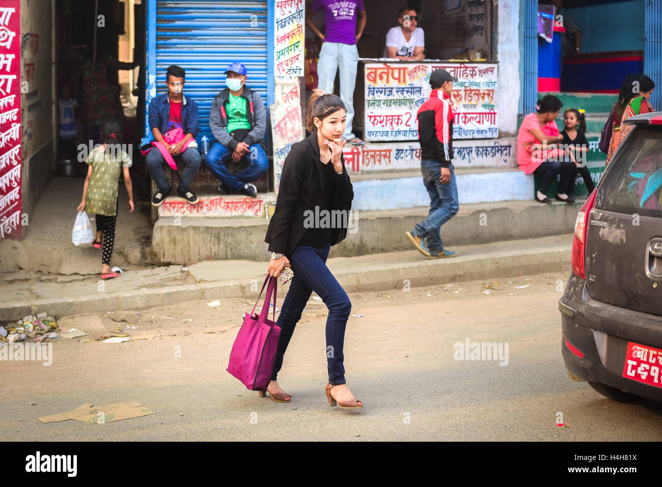 Young Nepali woman in casual fashion style crossing a street in the outskirts of Kathmandu, Nepal. - Stock Image