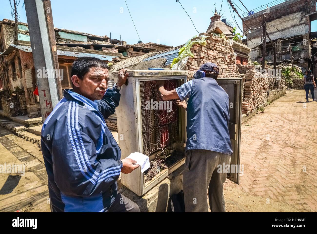 Technicians doing maintenance work on telephone network in Bhaktapur, Nepal. - Stock Image