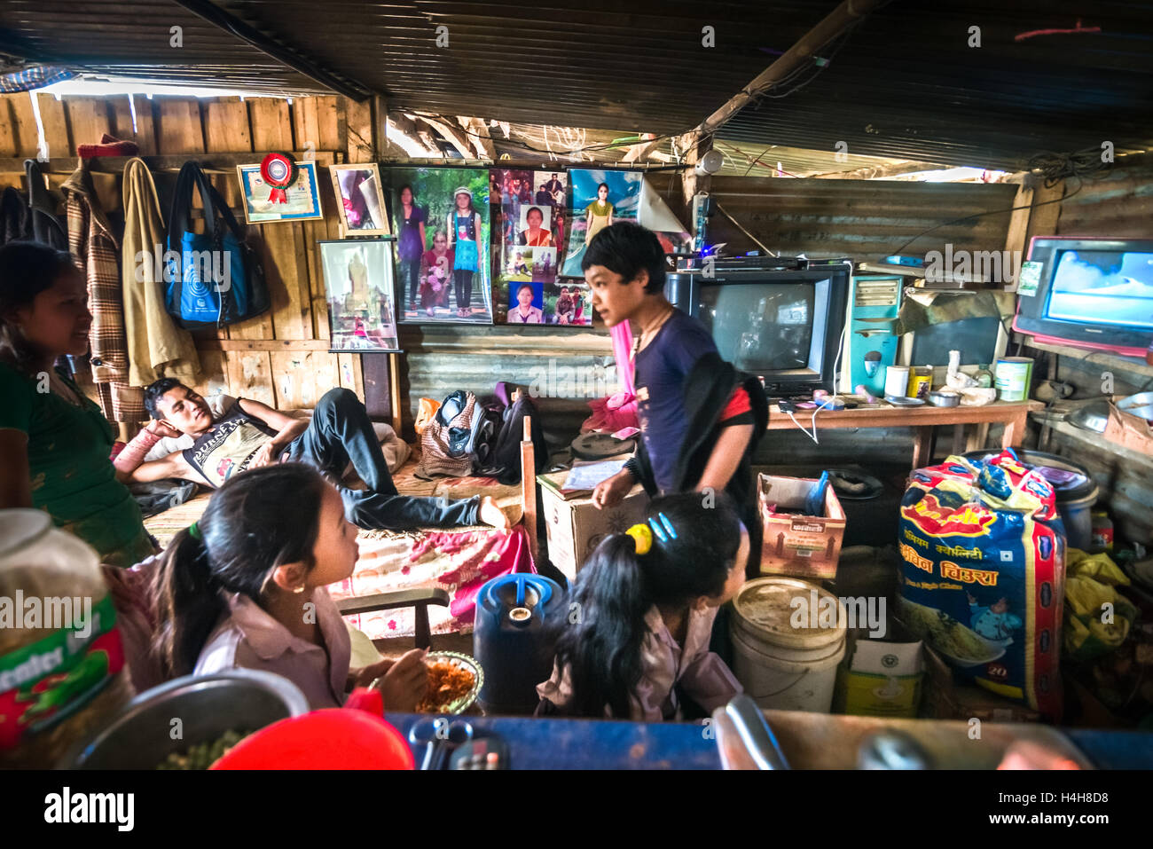 Children watching television inside their living room in Kavrepalanchowk district, Nepal. © Reynold Sumayku - Stock Image