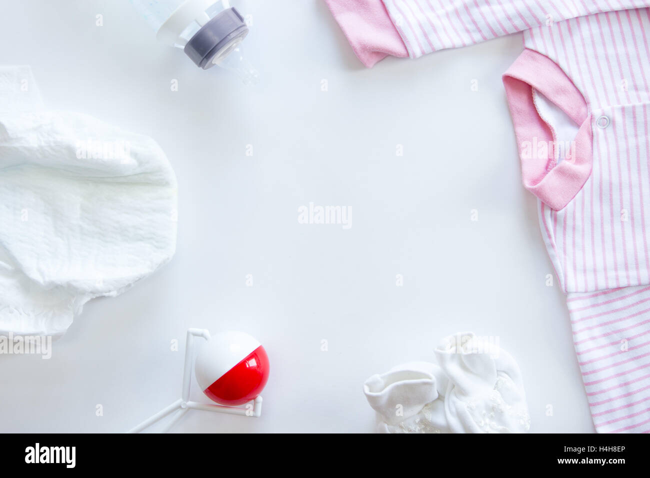 Set of baby supplies on table: diaper, beanbag, bottle, suit - Stock Image