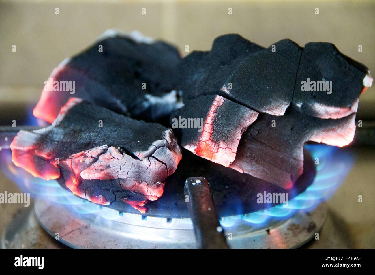 Charcoal burning over gas ring - Stock Image