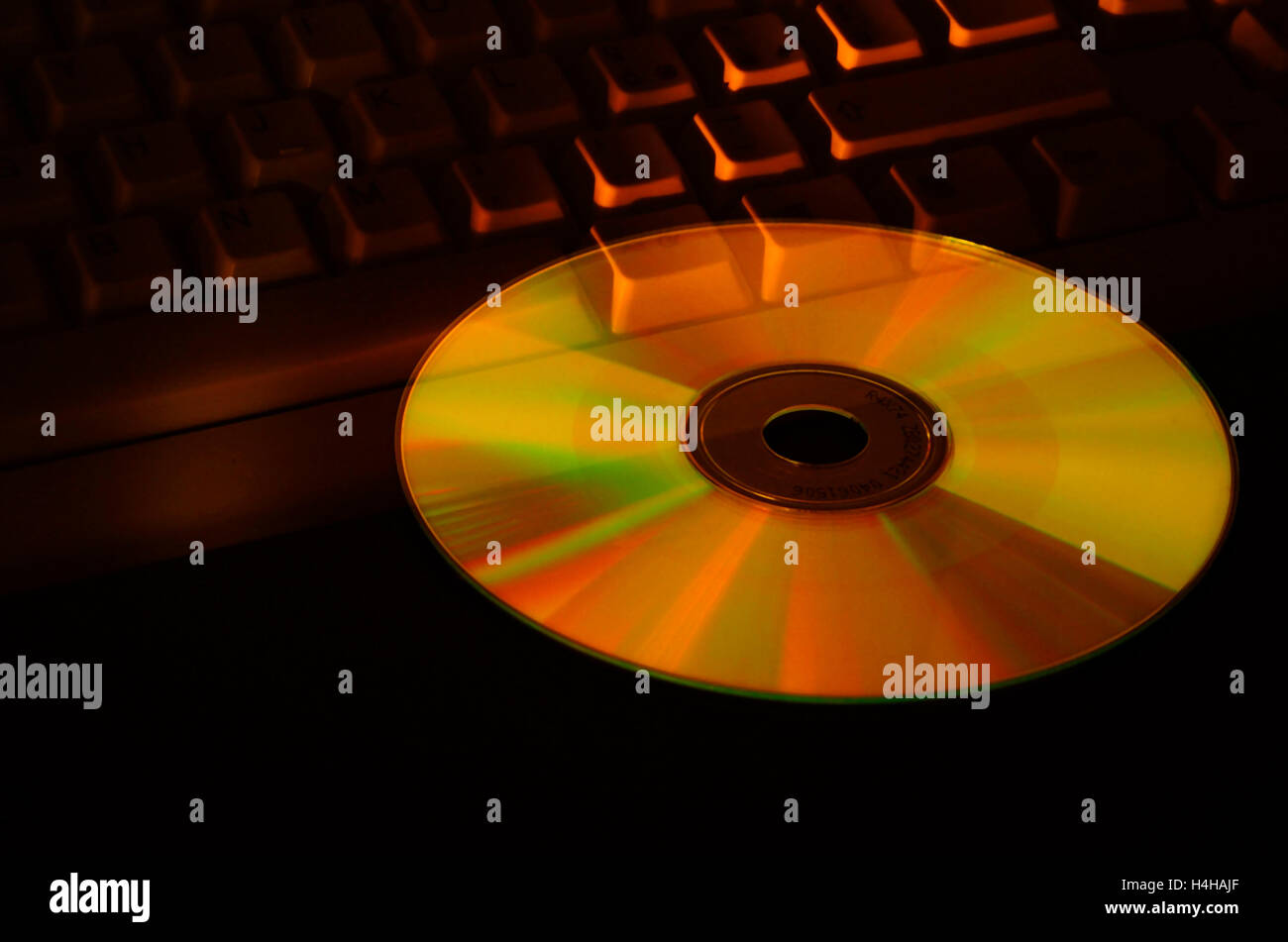 Compact disc flying on the keyboard - Stock Image