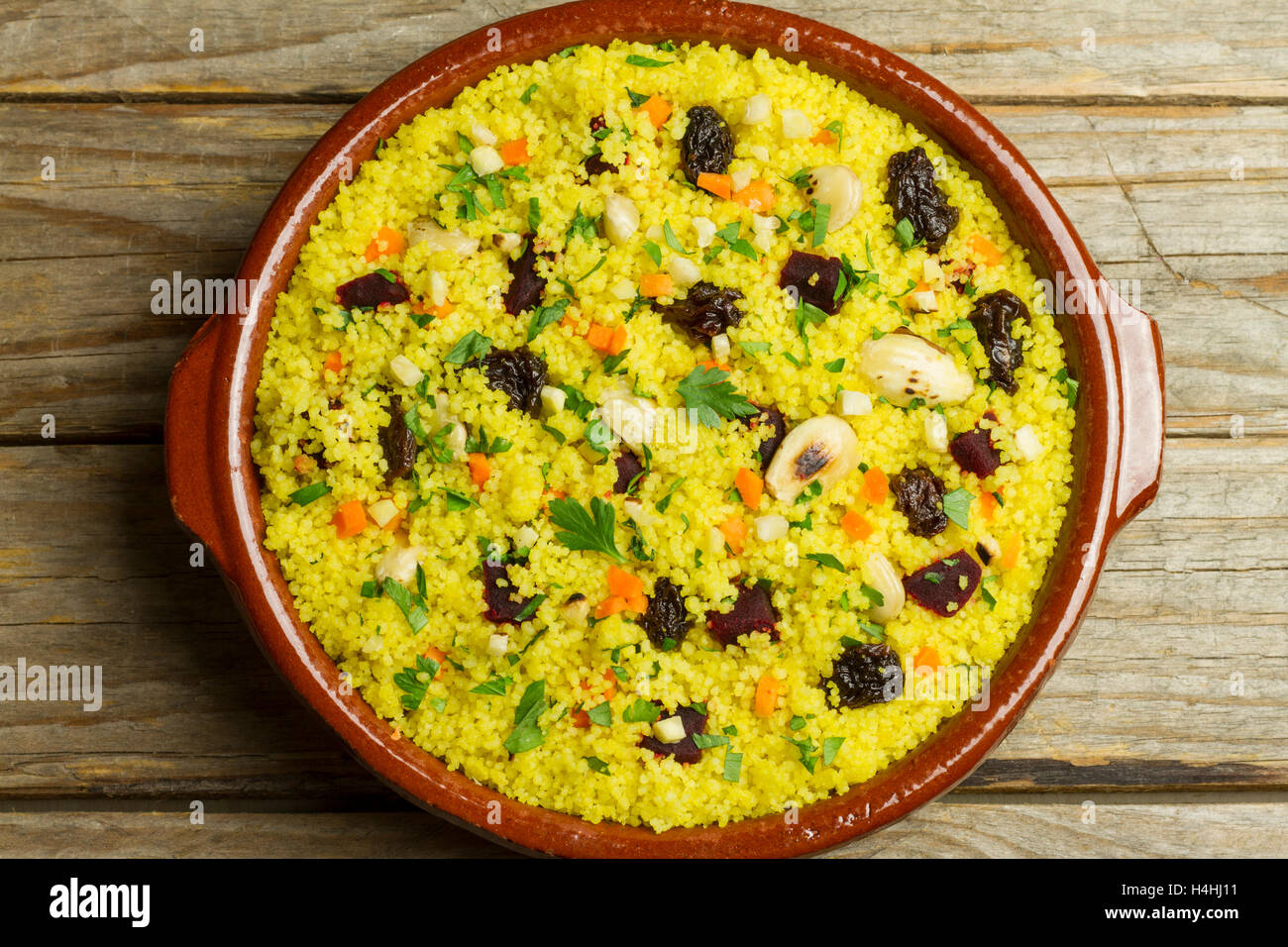 Couscous in an earthenware pot on a wooden table - Stock Image