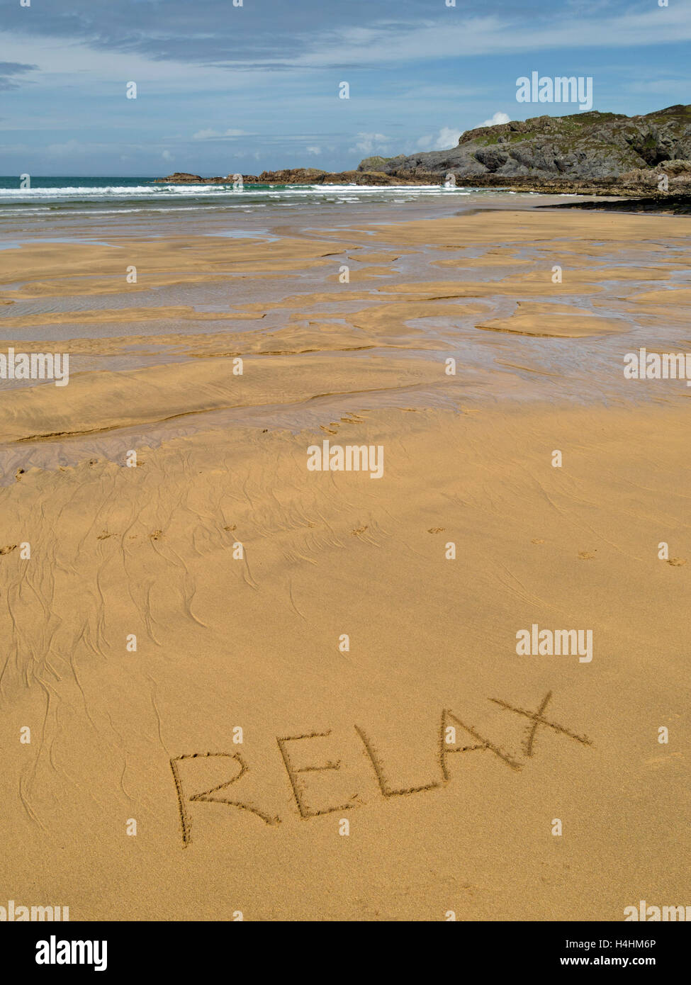 The word 'Relax' written in golden yellow sand of remote Scottish beach. - Stock Image