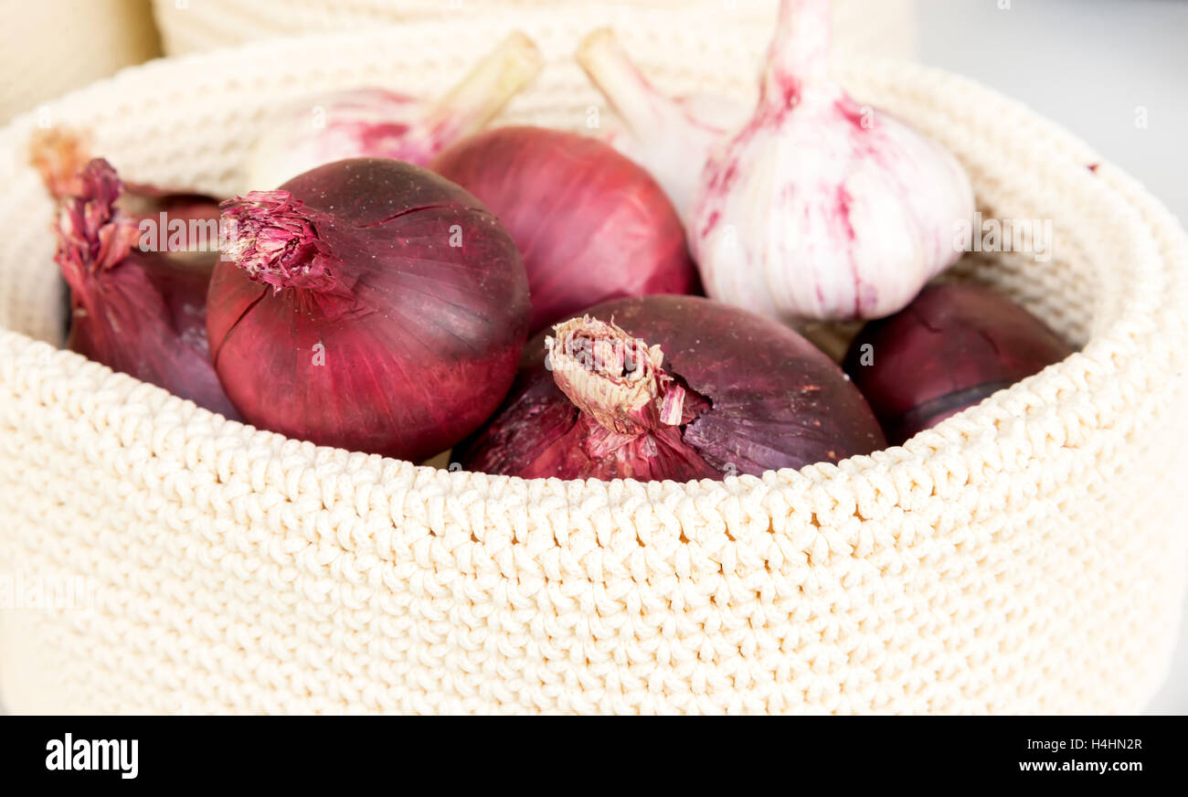 the red onions in a wicker basket close-up - Stock Image