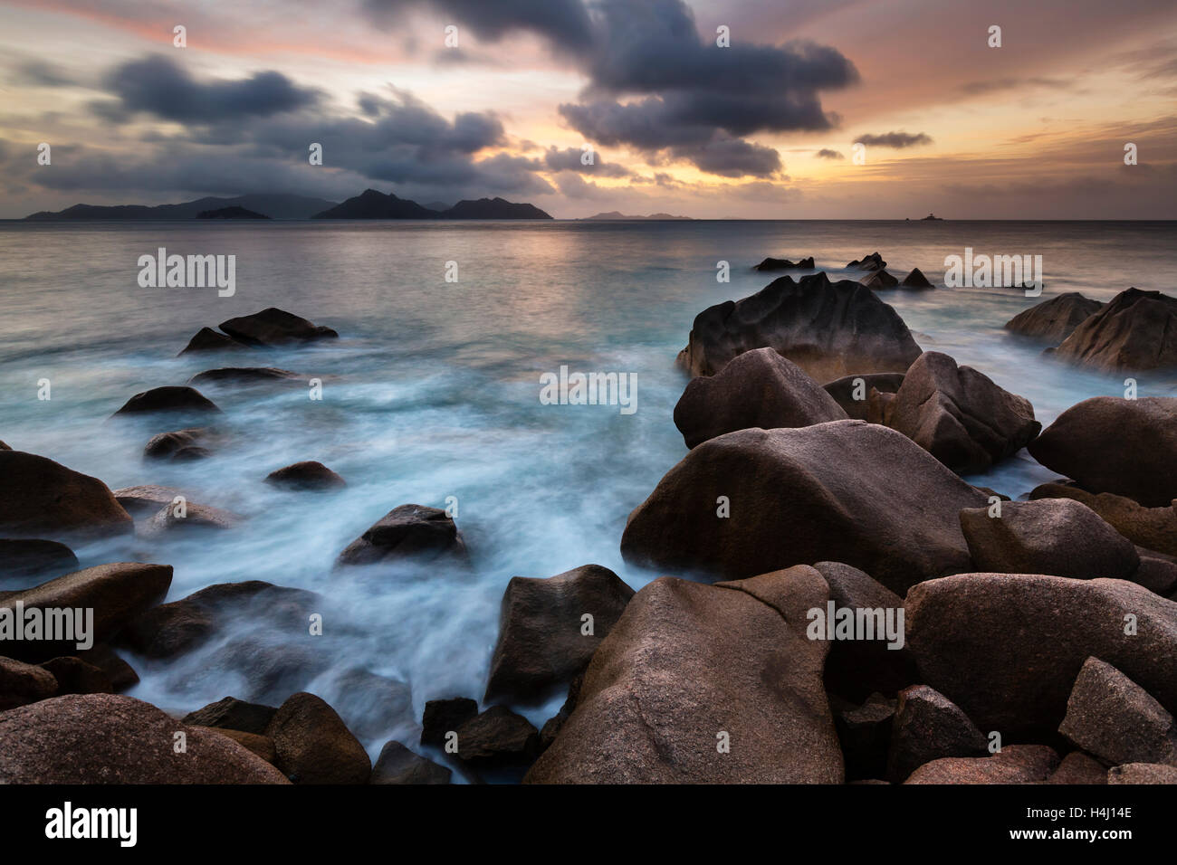 Sunset long exposure with view to Praslin from La Digue, Seychelles with granite rocks in the foreground Stock Photo