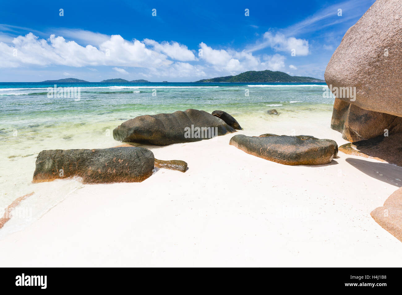 Anse Grosse Roche in La Digue, Seychelles with clear water and granite rocks - Stock Image