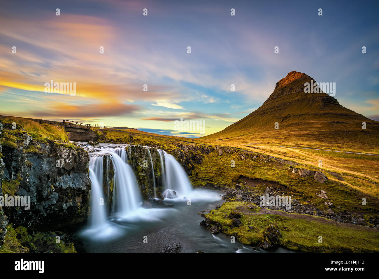 Summer sunset over the famous Kirkjufellsfoss Waterfall with Kirkjufell mountain in the background in Iceland. Long exposure. Stock Photo