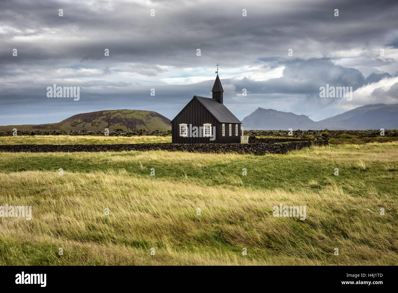 Scenery of black wooden church of Budir in Iceland with the pasture and mountains in the background - Stock Image