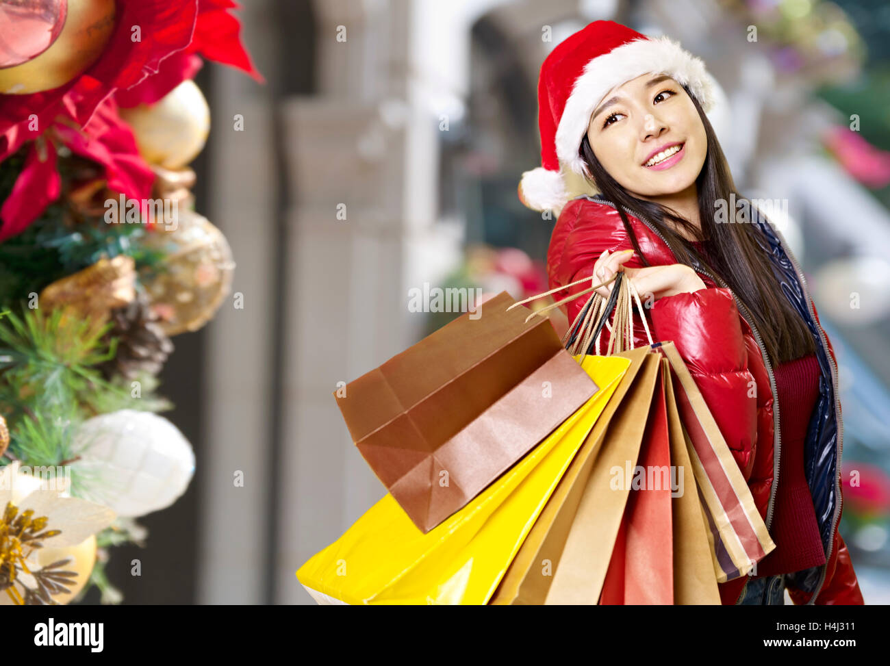 young asian woman carrying paper bags on shoulder during christmas shopping, happy and smiling. - Stock Image