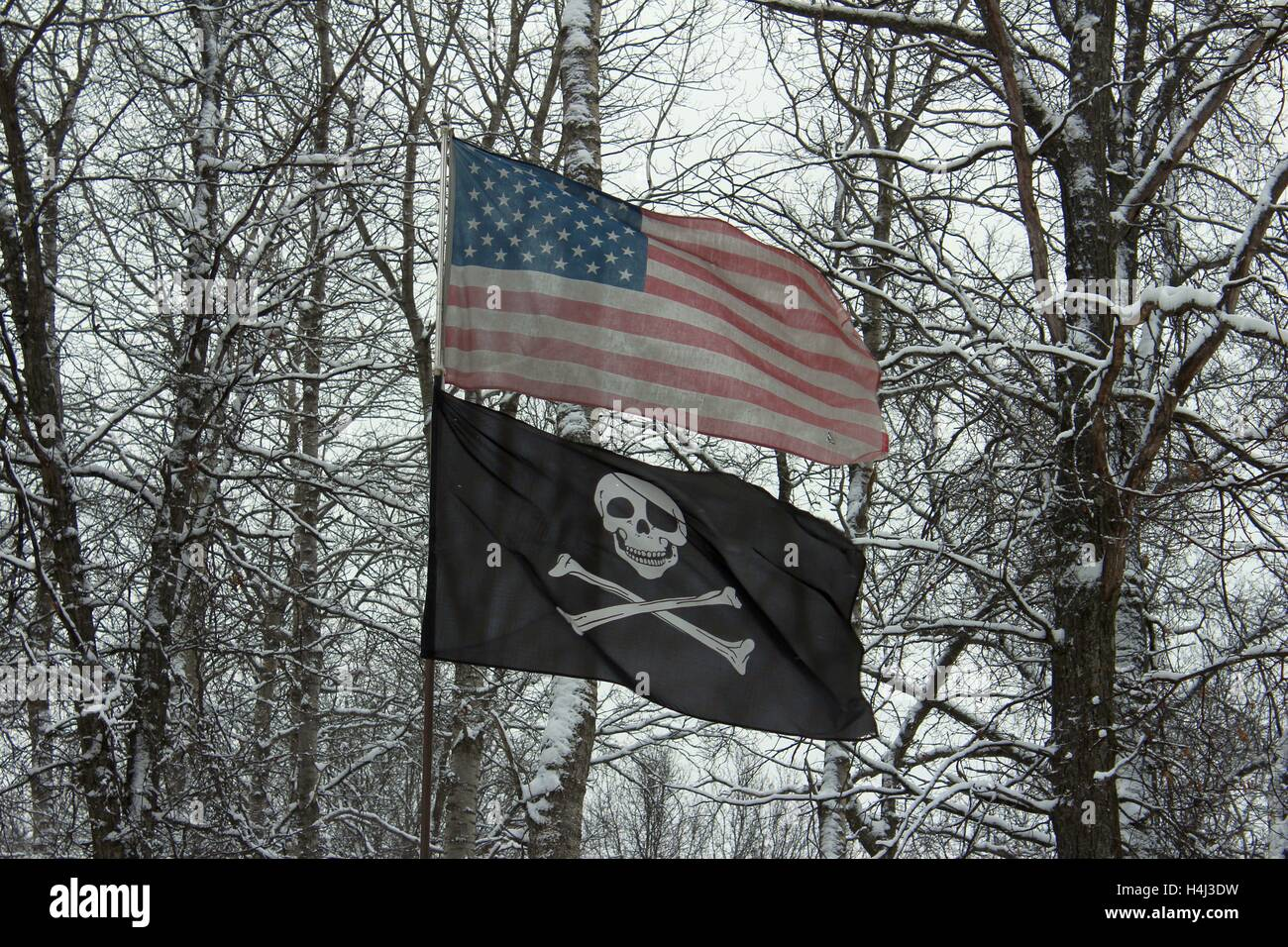 Faded Old Glory And Jolly Roger Share A Pole on a Winter's Day - Stock Image