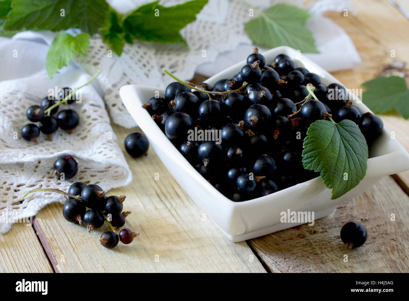 Ripe berries of a black currant in a bowl on a wooden table, selective focus. - Stock Image