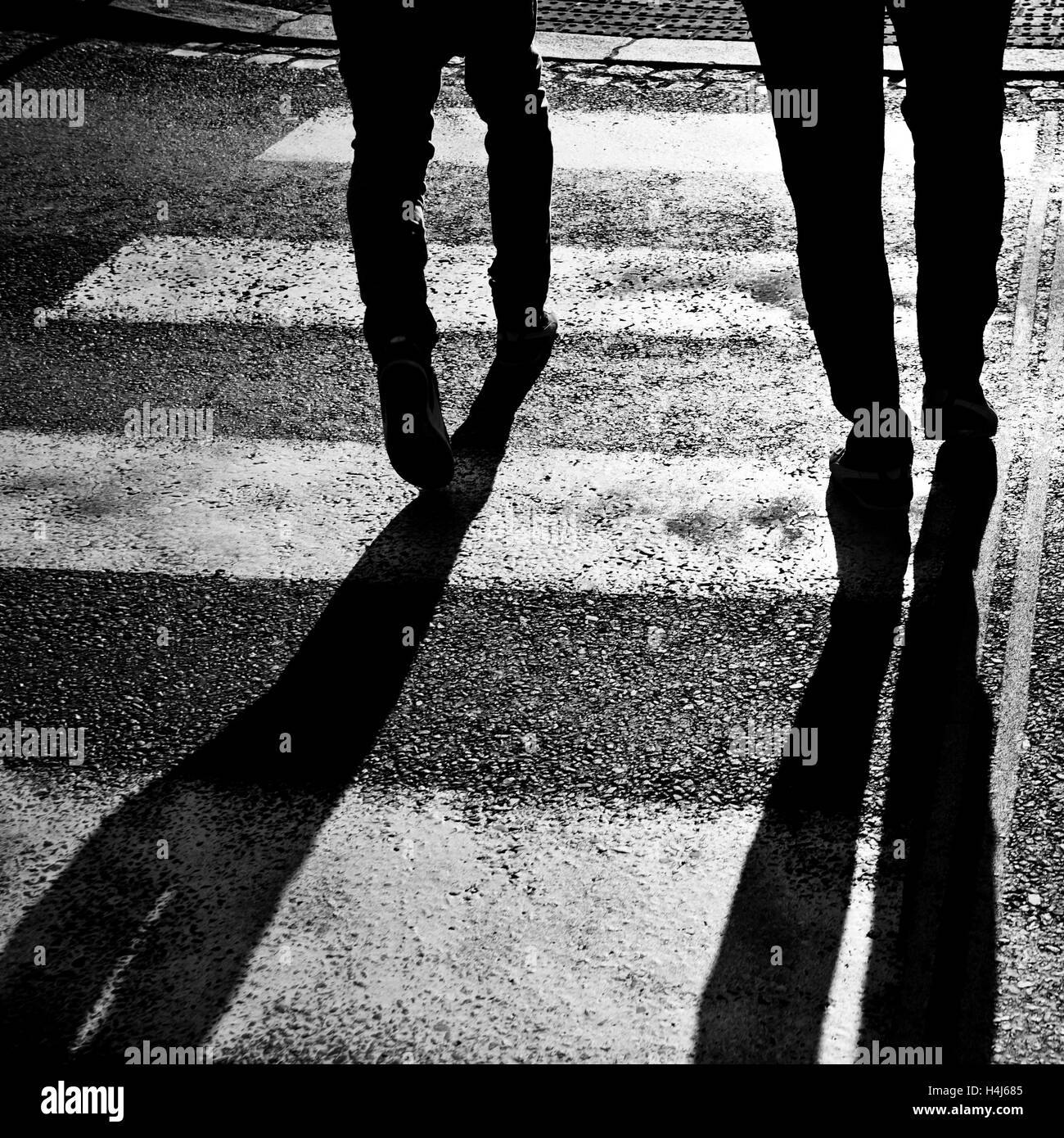 legs of two people and long shadow - Stock Image