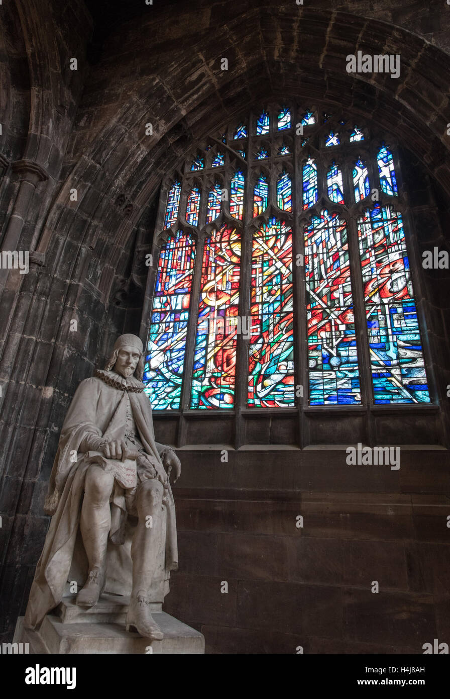 Statue of Humphrey Chetham and colorful stained glass window inside the famous  Manchester Cathedral. - Stock Image