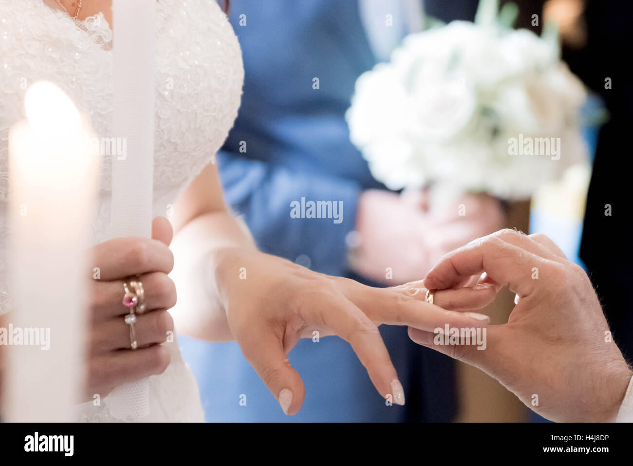 Wedding bride receiving wedding ring from groom in church. - Stock Image