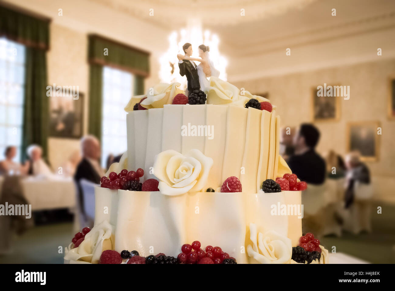 Wedding cake with male and female couple figurines - Stock Image