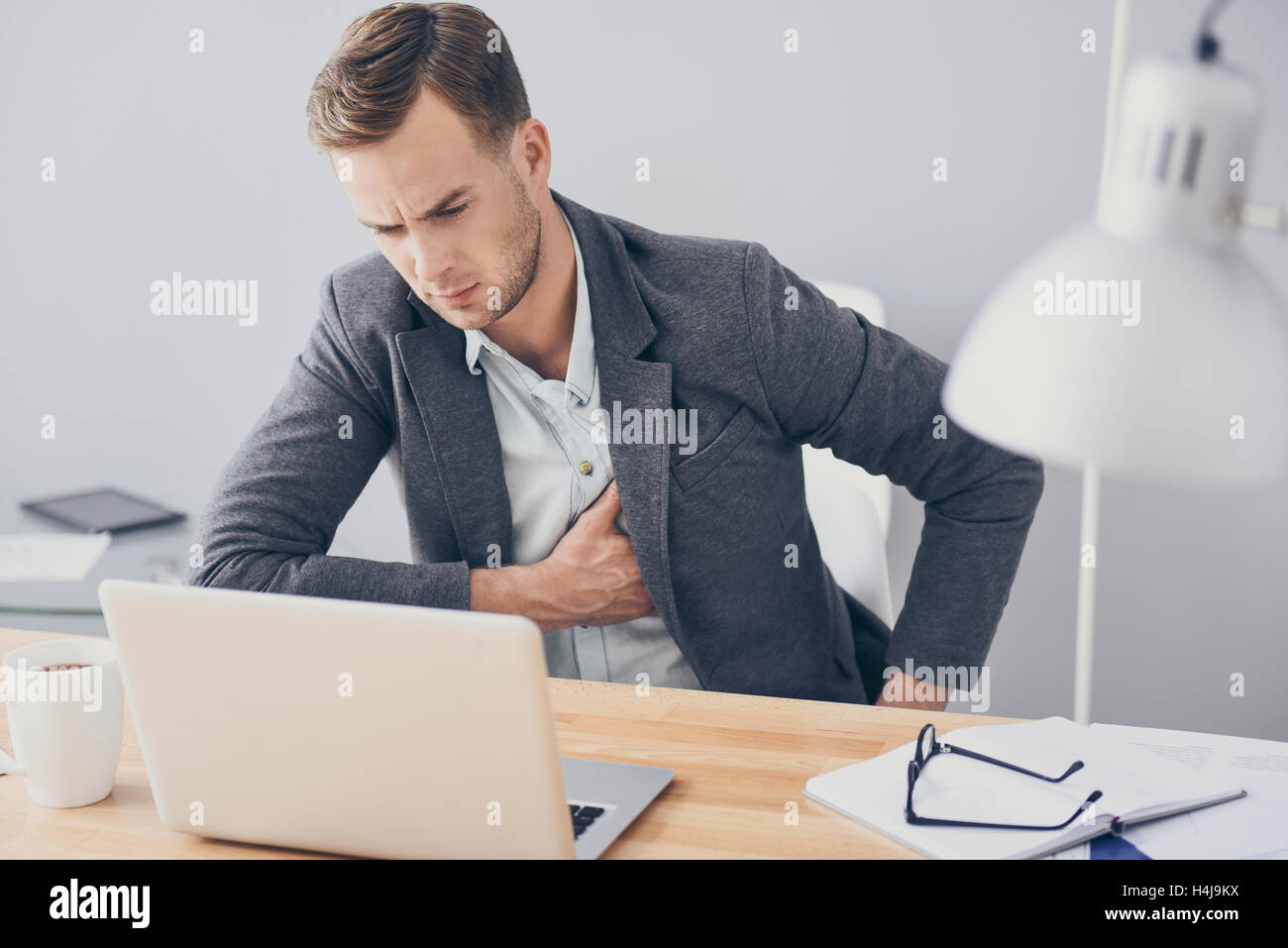 Young handsome man having heartache while working. - Stock Image