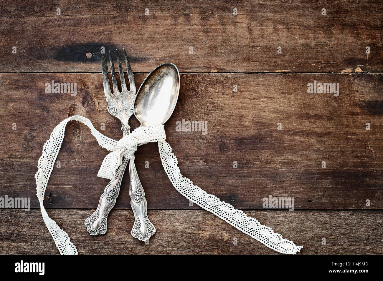 Antique Silverware Spoon And Fork Tied With Lace Ribbon Over A Rustic Old Wooden Background Grunge Like Feel