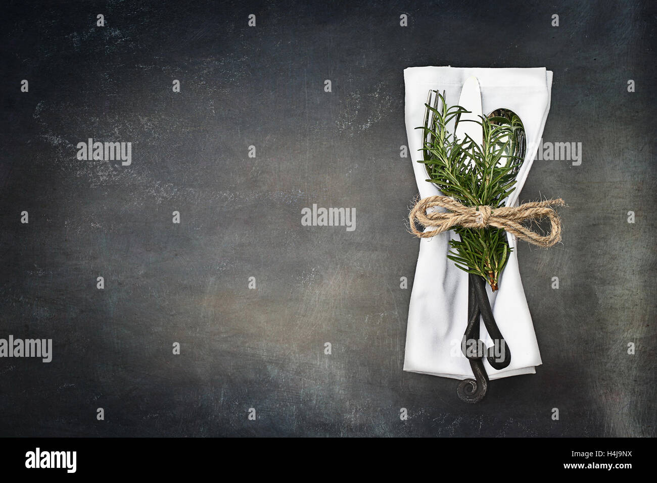 Antique silverware spoon and fork over a rustic grunge background. Image shot from overhead. - Stock Image