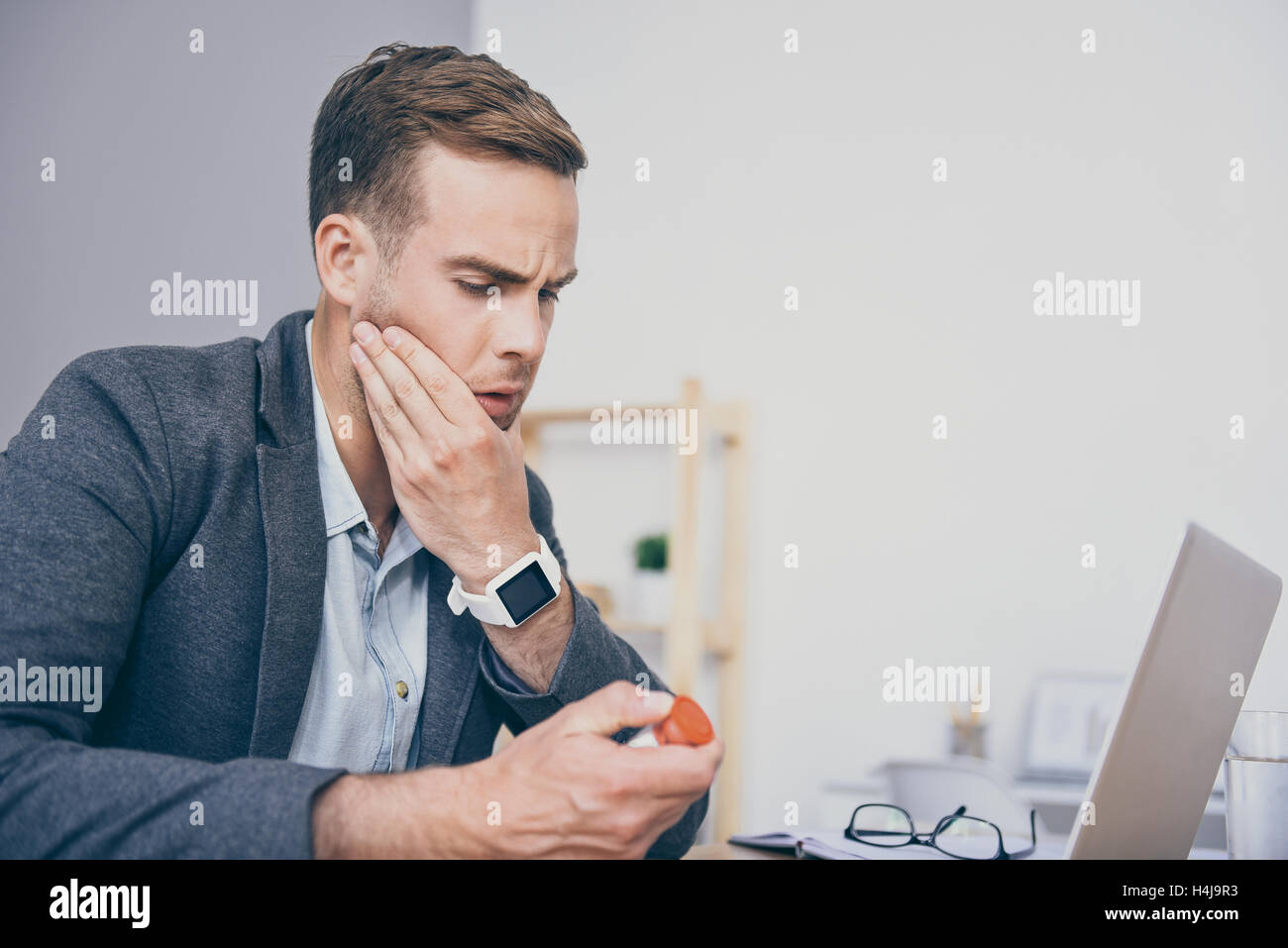 Unhappy young man holding medicines and sitting by the table. - Stock Image
