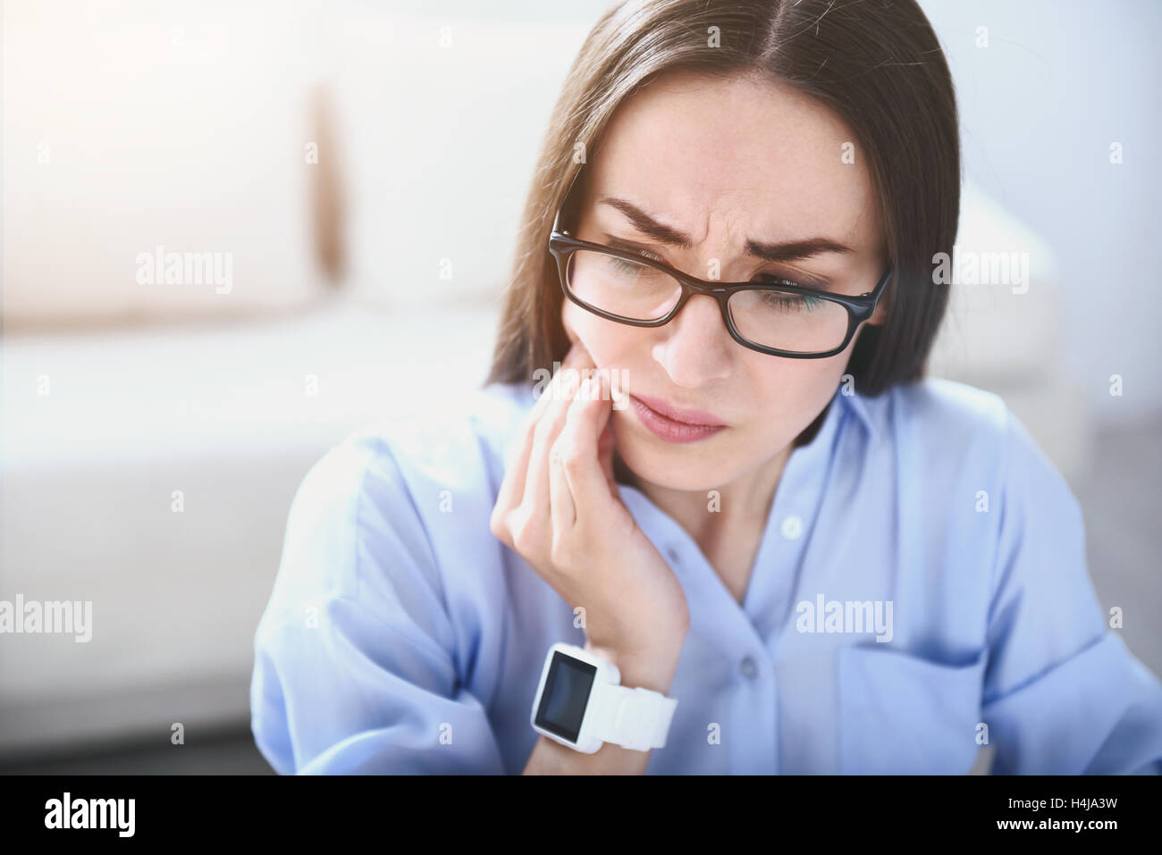 Tired young woman having toothache. - Stock Image