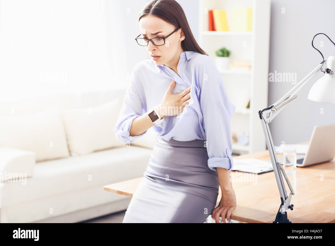 Pretty young woman having heartache and leaning on the table. - Stock Image