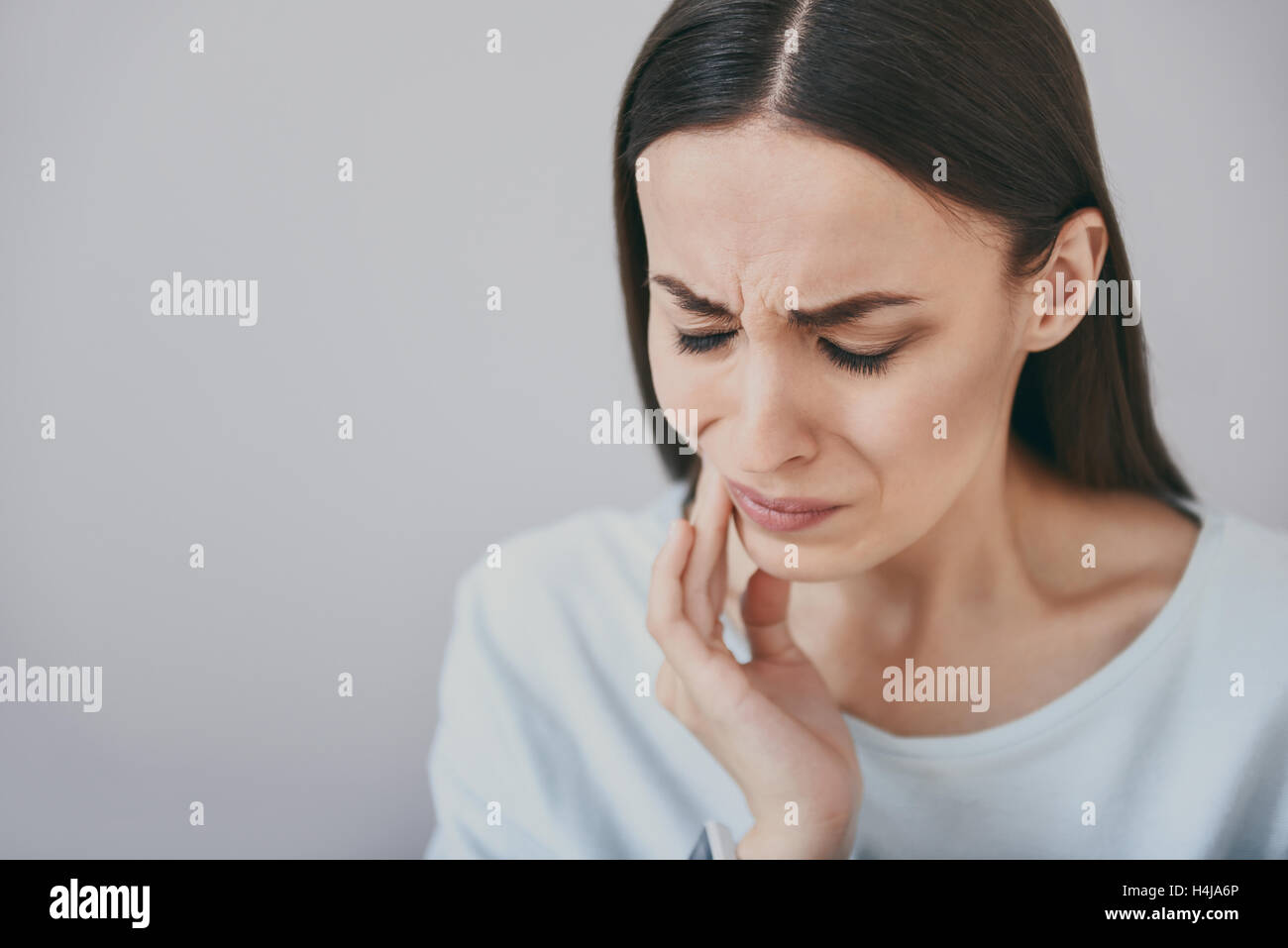 Close up of beautiful young woman which having toothache. - Stock Image