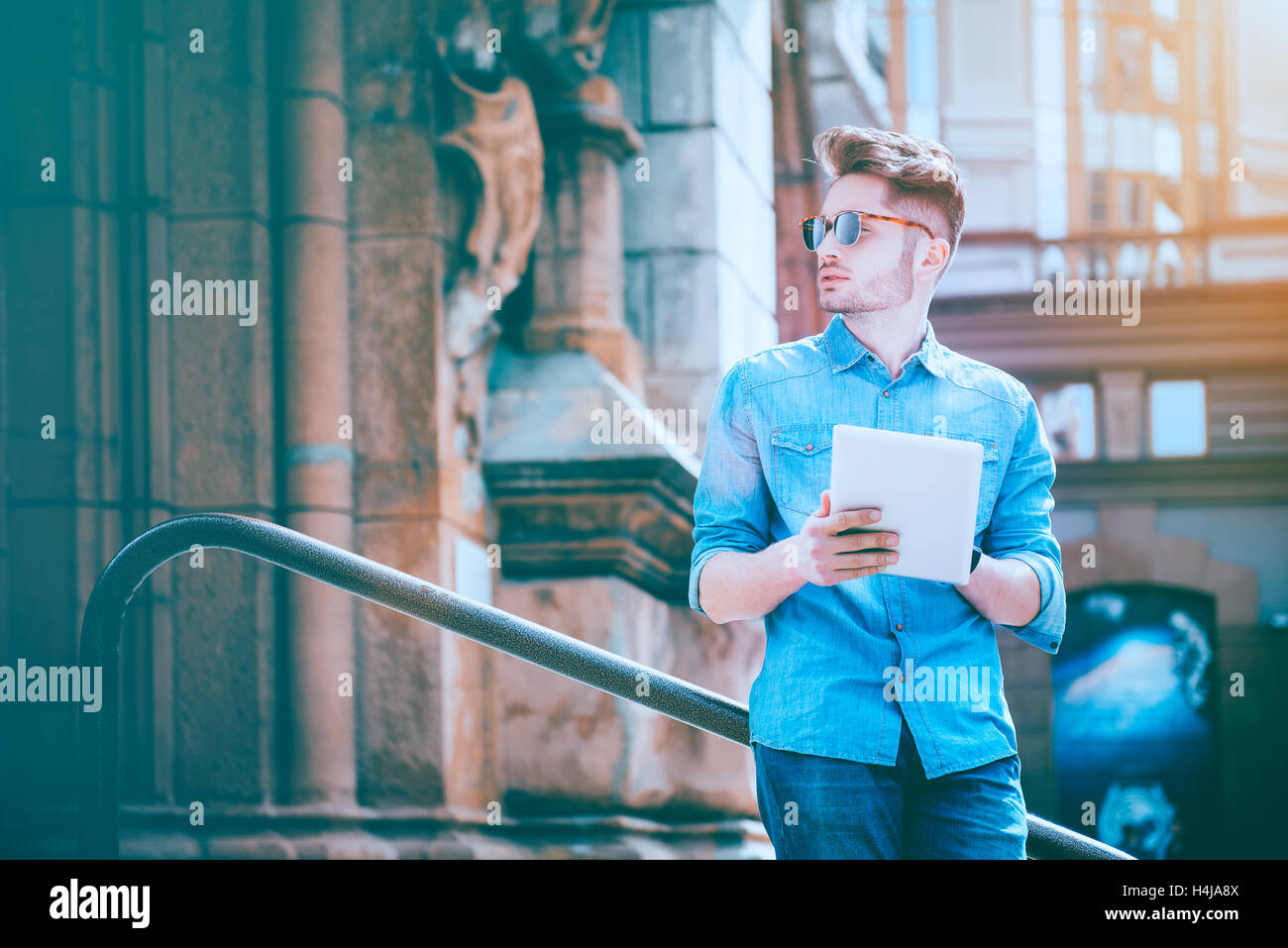 Handsome serious man using tablet - Stock Image